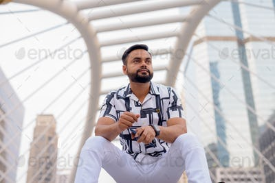 Young bearded Indian man thinking while sitting in the city outdoors