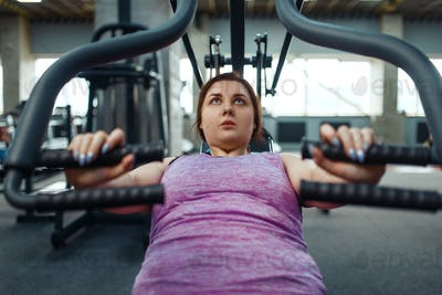 Overweight woman on exercise machine, top view