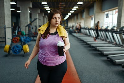 Overweight woman drinks diet cocktail in gym