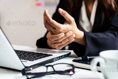 Stressed business woman suffering from wrist pain, Office syndrome concept