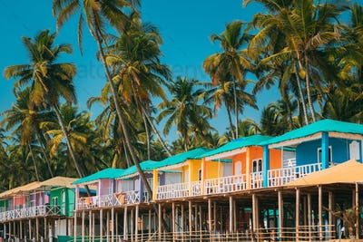 Canacona, Goa, India. Famous Painted Guest Houses On п Beach Against Background Of Tall Palm Trees