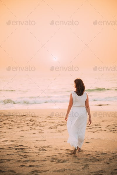 Goa, India. Young Caucasian Woman In White Dress Go To Sea Ocean And Looking Into Distance In Sunset