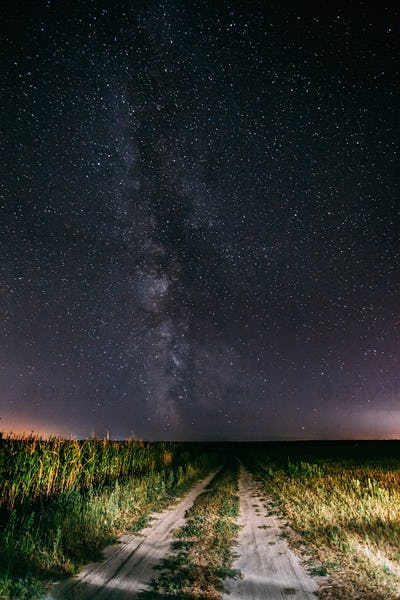 Night Starry Sky With Milky Way Glowing Stars Above Country Road In Countryside And Green Field