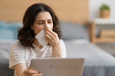 girl is holding paper tissue and blowing nose