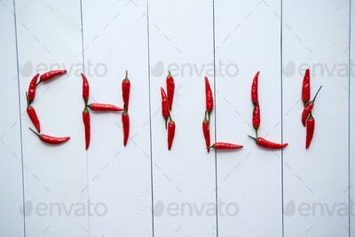 A word CHILLI formed with small red chilli peppers. Placed on white wooden table