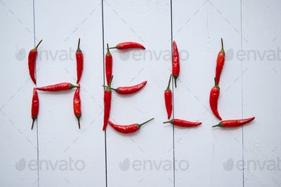 A word HELL formed with small red chilli peppers. Placed on white wooden table