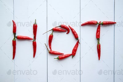 A word HOT formed with small red chilli peppers. Placed on white wooden table