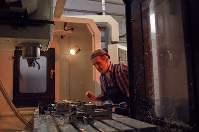 Mature worker working on lathe