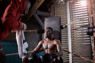 Coach training boxer in gym