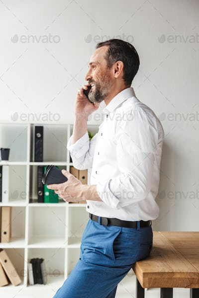 Attractive smiling businessman standing at the desk indoors