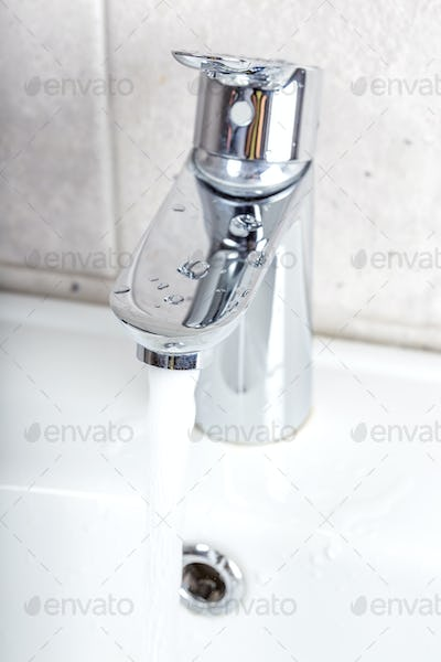 Flowing water from a modern designer chrome water tap
