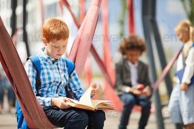 Schoolboy reading a book outdoors
