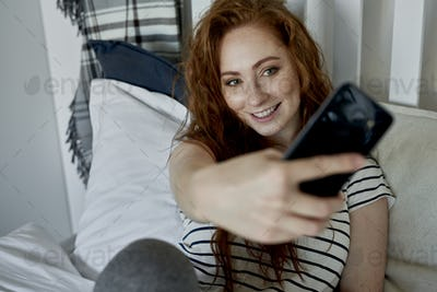 Woman taking selfie in the bedroom