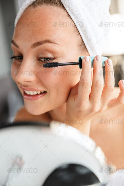 Photo of young joyful woman doing makeup while looking in mirror