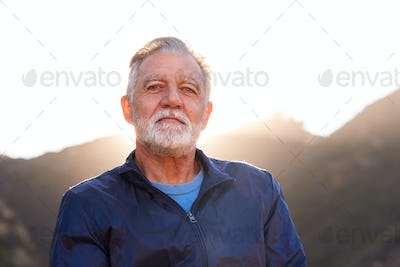 Outdoor Portrait Of Serious Hispanic Senior Man With Mental Health Concerns In Countryside