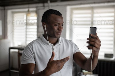 Happy black guy making video call to friend