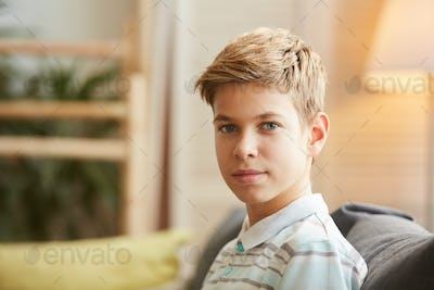 Boy sitting on sofa at home