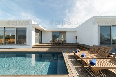 Lounge chairs in modern villa pool