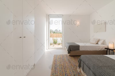 Double bedroom in modern villa with pool and deck