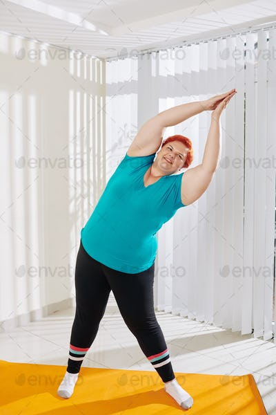 Plus size woman doing side bends