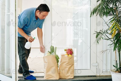 Man spraying delivered grocery packages