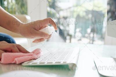 Office worker cleaning keyboard