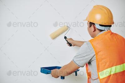 Painter applying white paint