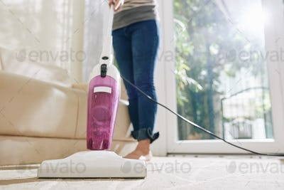 Housewife vacuum cleaning carpet