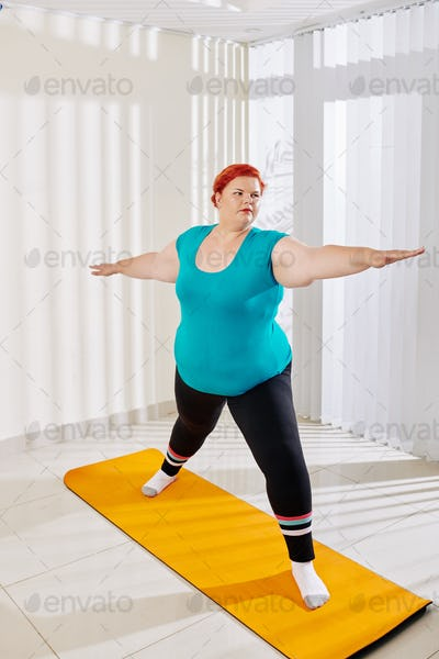 Plus size woman standing in warrior pose
