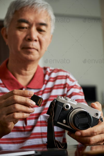 Man taking memory card out of camera