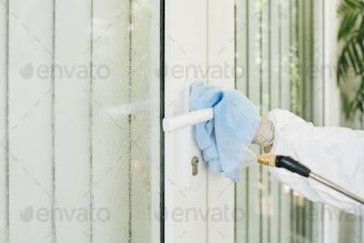 Worker disinfecting door handle