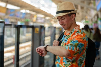 Young handsome tourist man checking the time at sky train station