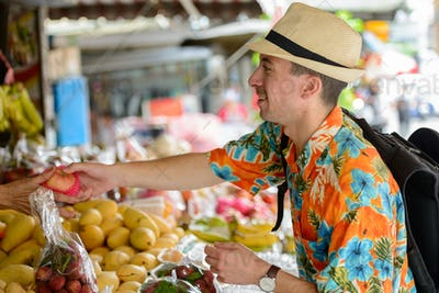 Happy young handsome tourist man buying at the street market