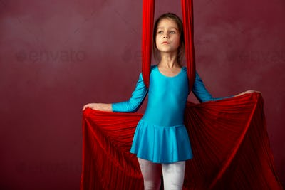 Fearless pretty little girl in a blue gymnastic suit