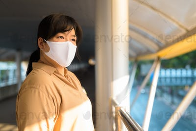 Overweight Asian woman with mask thinking at footbridge in the city