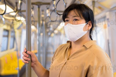 Overweight Asian woman with mask for protection from corona virus outbreak social distancing inside