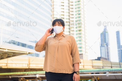 Overweight Asian woman with mask talking on the phone at skywalk bridge