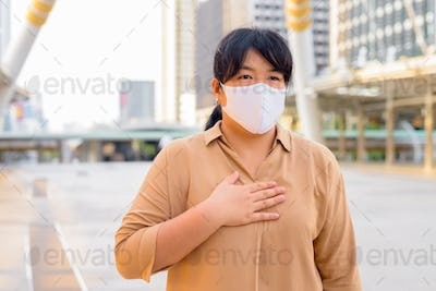 Overweight Asian woman wearing mask with hand on chest in the city
