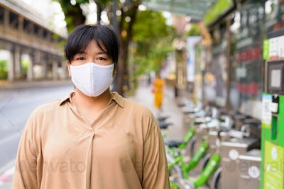 Overweight Asian woman with mask for protection from corona virus outbreak at public bicycle service