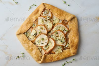 Pear galett with blue cheese, savory pie, marble table, top view