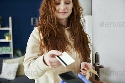 Woman using credit card to pay for a delivery
