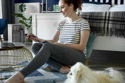 Woman using laptop at home on the floor