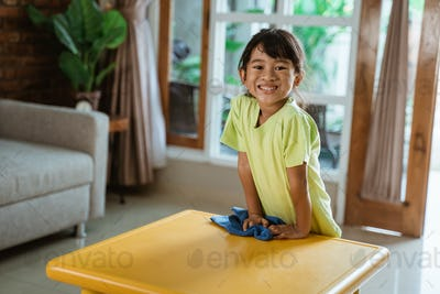 kid smiling to camera while doing house cleaning