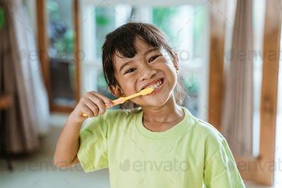 asian little girl brush her teeth