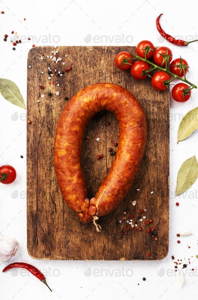 Smoked sausage on white kitchen table background with aromatic herbs and spices