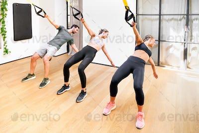 Three athletes doing Trx power pull exercises