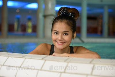 Face of happy young beautiful Asian tourist woman relaxing at the spa