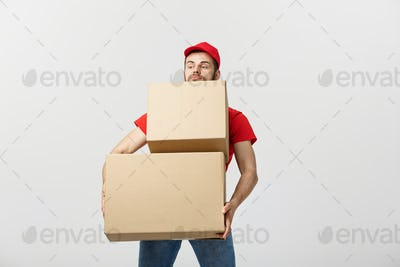 Delivery man doing surprise gesture holding cardboard boxes