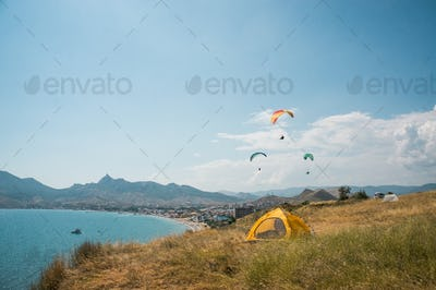 People Flying on Paragliders at Sea, Camping on Foreground, Ukraine, Crimea