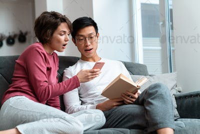 Photo of shocked multinational couple reading book and using smartphone